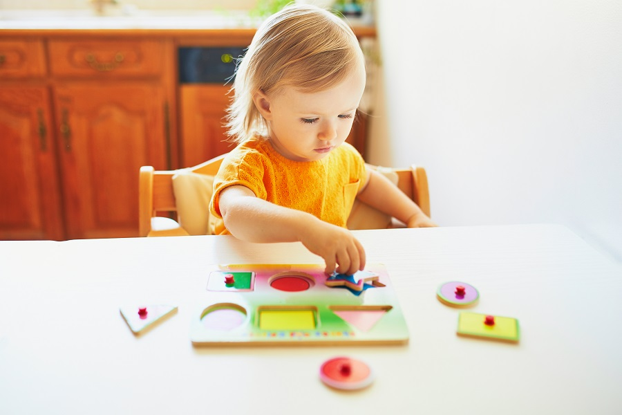 Adorable toddler girl doing wooden puzzle
