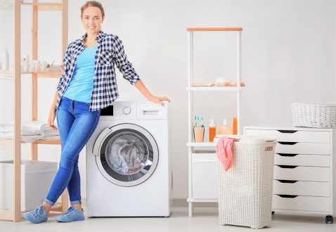 Young woman near washing machine in laundry room