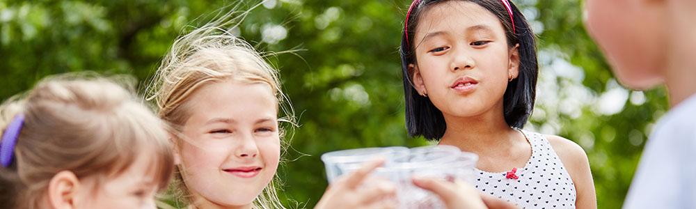 Gruppe Kinder beim Wasser trinken im Sommer